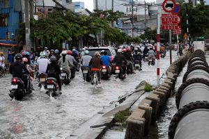 HO CHI MINH CITY VIET NAM- OCT 18 2016: Awful flooded street at Asian city crowd of people ride motorcycle wade in water from tide on road climate change make sea level rise Vietnam